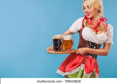 Young sexy Oktoberfest girl - waitress, wearing a traditional Bavarian dress, serving big beer mugs on blue background.
