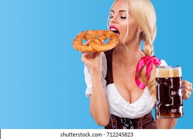 Young sexy Oktoberfest girl - waitress, wearing a traditional Bavarian dress, serving big beer mugs and eating pretzel on blue background. Copy space.