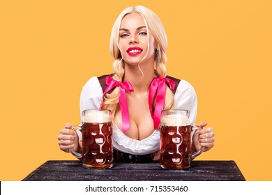 Young sexy Oktoberfest girl - waitress, wearing a traditional Bavarian dress, serving big beer mugs on orange background.