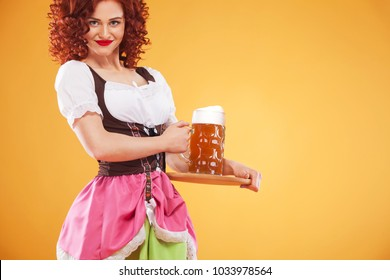 Young sexy Oktoberfest waitress, wearing a traditional Bavarian dress, serving big beer mugs on yellow background.