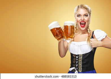 Young sexy Oktoberfest waitress, wearing a traditional Bavarian dress, serving big beer mugs on blue background with copy space
