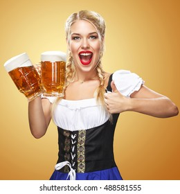 Young sexy Oktoberfest waitress, wearing a traditional Bavarian dress, serving big beer mugs on blue background. Thumbsup