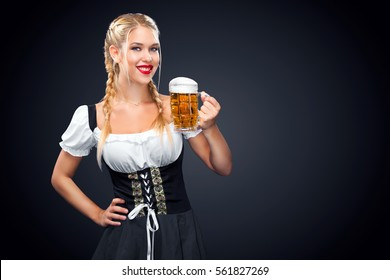 Young sexy Oktoberfest waitress, wearing a traditional Bavarian dress, serving big beer mugs on black background.