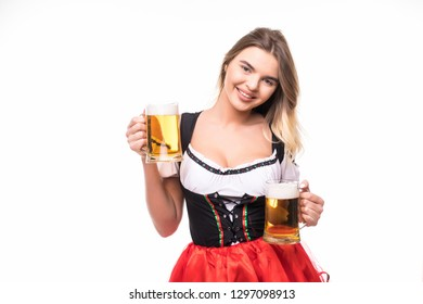 Young sexy Oktoberfest woman wearing a traditional Bavarian dress dirndl serving two beer mugs with smile on white background.