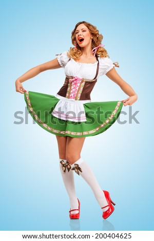 8c190533c75c Young sexy Oktoberfest woman wearing a traditional Bavarian dress dirndl  dancing and singing on blue background