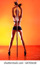 Young sexy pole dance woman. Vibrant red light.