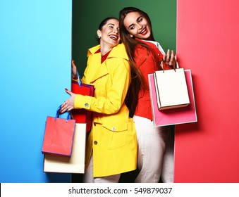 young sexy pretty funny women or model girls with long beautiful hair on happy face in colorful red and yellow coats with fashion makeup holding bags on green blue studio background