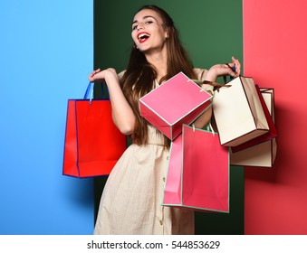 young sexy pretty woman or model girl with long beautiful blonde hair on smiling face in beige vintage dress and fashion makeup holding bags on colorful studio background