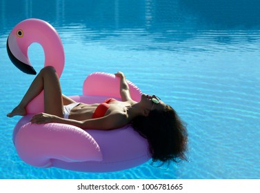 Young sexy pretty woman relaxing in a swimming pool leisure on a giant inflatable giant pink flamingo float mattress in red bikini