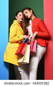 young sexy pretty women or model girls with long beautiful hair on serious face in colorful red and yellow coats with fashion makeup holding bags on green blue studio background