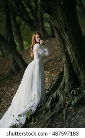 Young sexy redhead woman in white bridal vintage dress