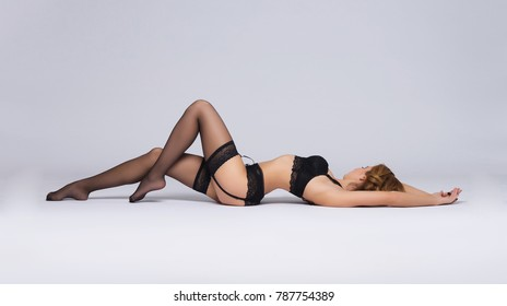 Young, sexy and seductive woman in erotic lingerie posing in studio. Girl in beautiful underwear.