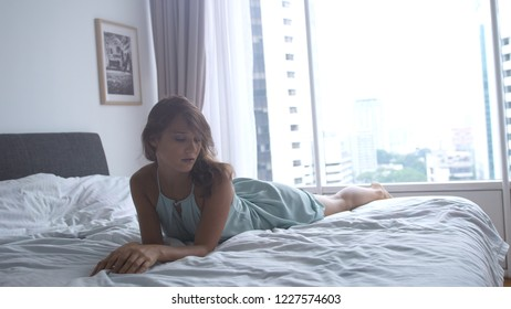 Young sexy sensual brunette girl lies on the bed, temptation, beautiful female body, daylight, near panoramic window in apartment with city view