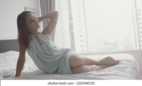Young sexy sensual brunette joyful girl sits on the bed with closed eyes, temptation, beautiful female body, daylight, near panoramic window in apartment with city view