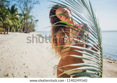 200cee7e9b3c3 young sexy skinny woman in white bikini swimwear holding leaf of palm tree  sunbathing on tropical