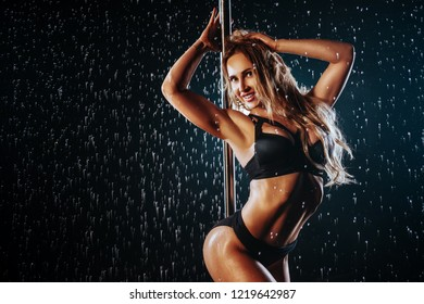 Young sexy slim blond woman pole dancing in dark interior with water