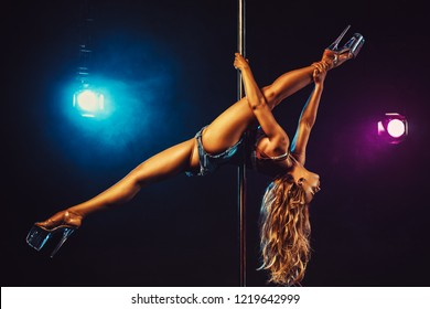 Young sexy slim blond woman pole dancing in dark interior with smoke and light flares