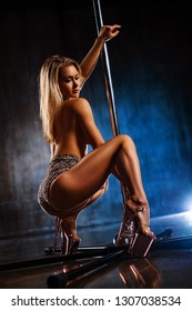 Young sexy slim blond woman pole dancing in dark interior on stone wall background
