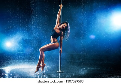 Young sexy slim brunette woman pole dancing in dark interior with smoke and water