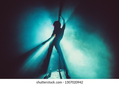 Young sexy slim pole dance woman silhouette in smoke and blue light