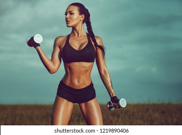 Young sexy slim sports woman training on field and sky background. Tattoo on hand.