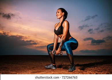 Young sexy slim sports woman doing squats outdoors on field and sky background at twilight. Tattoo on body.