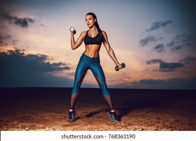 Young sexy slim sports woman training on field and sky background at twilight. Tattoo on body.