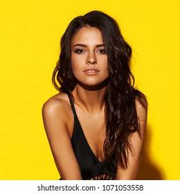 Young sexy slim tanned woman in black swimsuit posing against yellow background. Fashion portrait of beautiful girl with long wavy brunette hair. Swimwear or bikini model