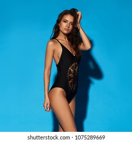 Young sexy slim tanned woman in black swimsuit posing against blue background. Full length fashion portrait of beautiful girl with long wavy brunette hair. Swimwear or bikini model