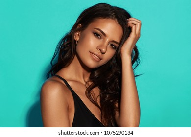 Young sexy slim tanned woman in black swimsuit posing against blue background. Closeup Fashion portrait of beautiful girl with long wavy brunette hair. Swimwear or bikini model