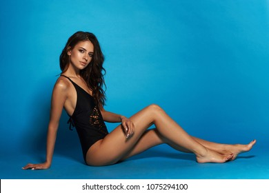 Young sexy slim tanned woman in black swimsuit posing and sitting on blue background. Fashion portrait of beautiful girl with long wavy brunette hair. Swimwear or bikini model