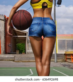Young and sexy slim woman with a basketball in hand. Back view. Female ass and basketball. Fitness, sport, healthy lifestyle.