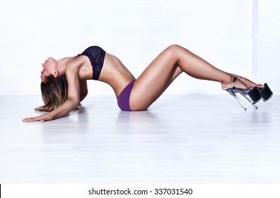 Young sexy slim woman dancer in lingerie stretching on white wall background