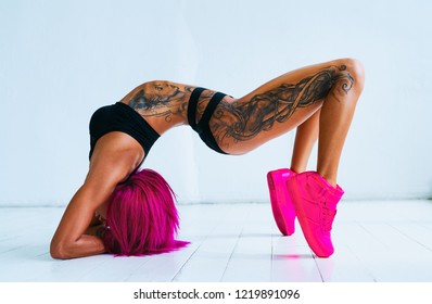 Young sexy slim woman with pink hair sports stretching in bright white interior. Tattoo on body.