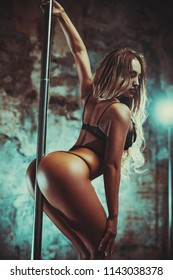 Young sexy slim woman pole dancing on stone wall background