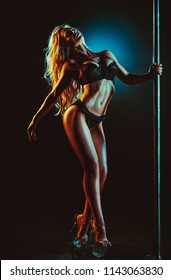 Young sexy slim woman pole dancing in dark interior with warm and cool lights