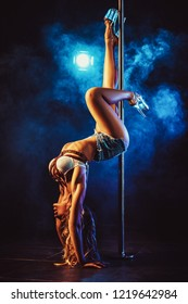 Young sexy slim woman pole dancing in dark interior with blue smoke