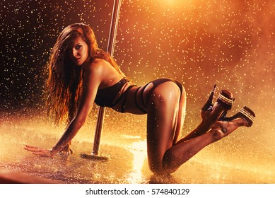 Young sexy slim woman pole dancing with red lights and water rain