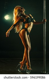 Young sexy slim woman pole dancing in dark interior with lights
