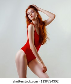 Young sexy slim woman in red swimsuit posing in studio. Full length fashion portrait of beautiful girl with long wavy red hair. Swimwear or bikini mode. Copy space, gray background