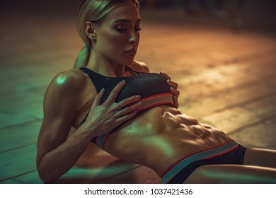 Young sexy slim woman showing abdominal muscles.