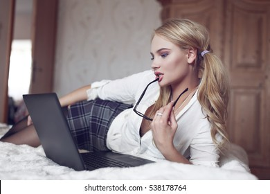 Young sexy smart blonde woman flirting online on laptop, lying on bed in bedroom