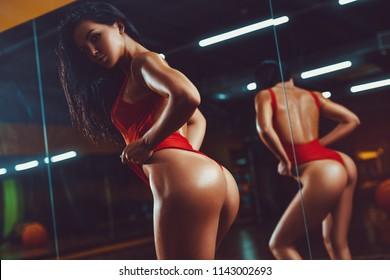 Young sexy sports woman posing in gym interior with reflection in mirror