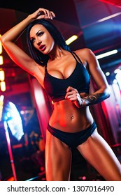 Young sexy sports woman posing in gym interior with red vibrant lights. Tattoo on body.