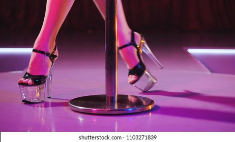 young sexy striptease dancer moving in high heels shoes on stage in strip night club, Pole dancing.