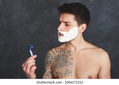 Young sexy tattooed man with foam on face looking at razor with blunt blade in hand. Topless guy with unpleased look shaving, gray studio background, copy space
