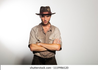 Young sexy  unshaven man in cowboy hat. Romantic image of a vintage traveler and adventurer. Guy crossed arms over his chest.