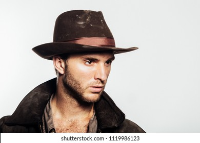 Young sexy  unshaven man in cowboy hat. Stylish dark brown clothes on a white background. Romantic image of a vintage traveler and adventurer.