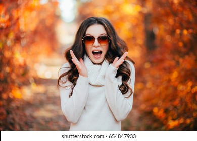 Young sexy woman in the autumn forest, happy, smiling and surprised. Woman is in sun glasses.