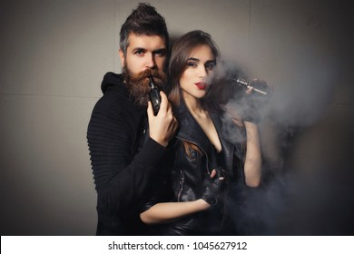 Young sexy woman with bearded man are vaping together. Relationship and vape addiction concept with copy space. Young man and woman blowing smoke to join it in one cloud at black studio background.